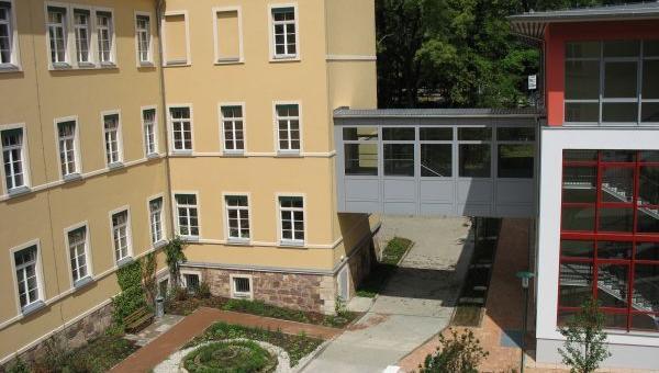 Ein gelbes Schulgebäude mit einem schwebenden Übergang